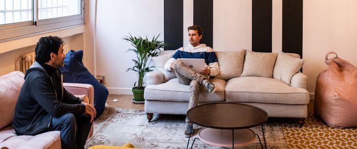 Deux coworkers en pleine discussion dans un espace convivial et chaleureux de coworking